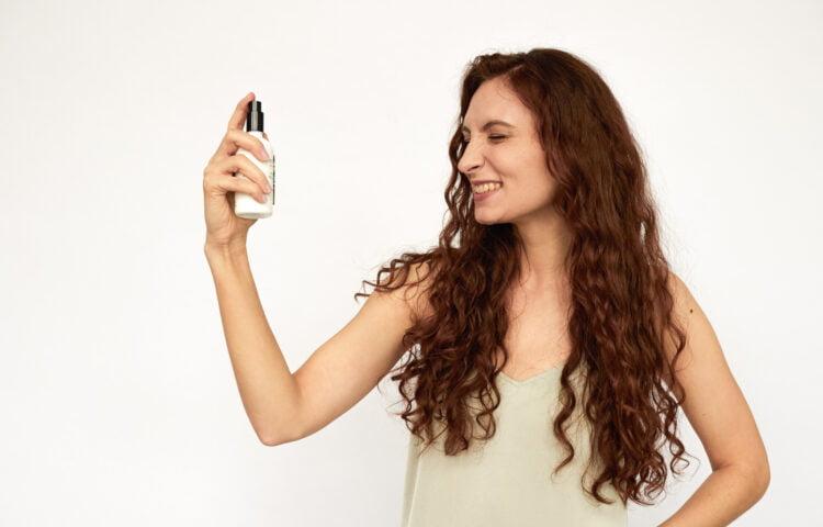 Kobieta nawilżająca skórę hydrolatem.